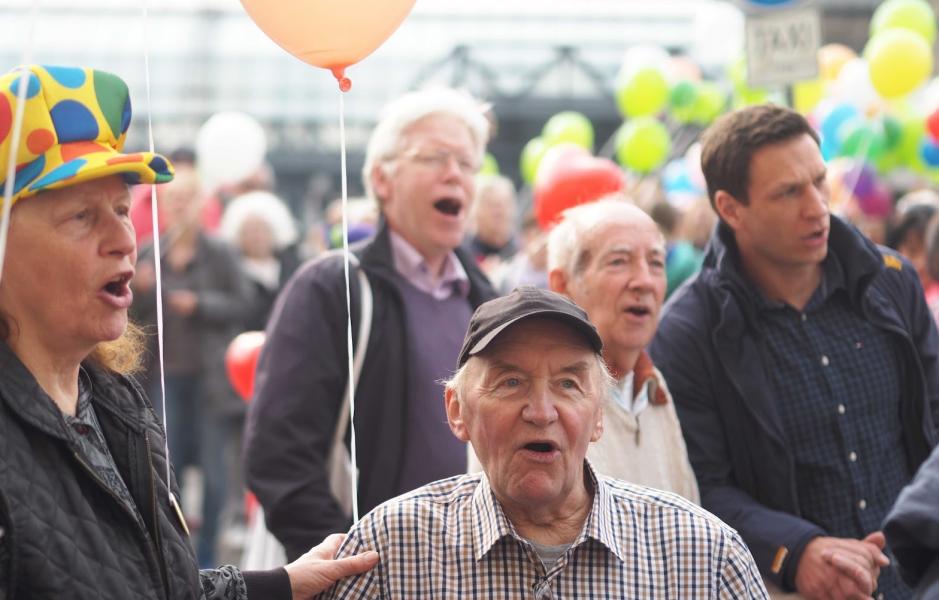 Mehrere Personen singen, im Hintergrund Luftballons. Foto der Konfetti-Parade für den Konfetti-Fotowettbewerb
