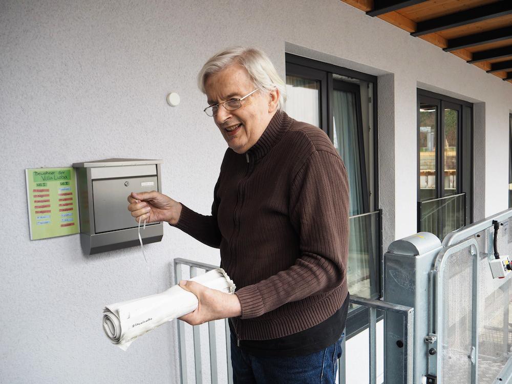 Der ehemalige Postbote Peter holt die Tageszeitung von der Veranda