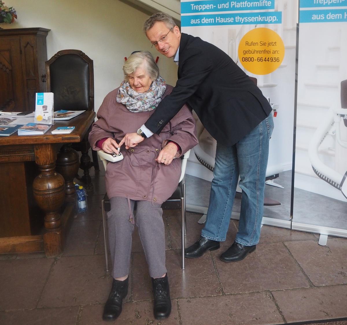 Noch braucht sie ihn zum Glück nicht: Oma probiert aus, wie man im Treppenlift sitzt