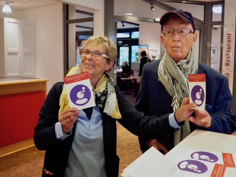 Eine pflegende Angehörige mit ihrem Mann, der Demenz hat, bei einem Konzert