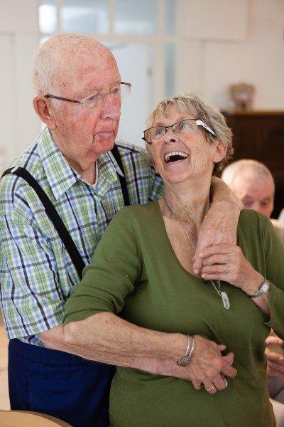 Eine pflegende Angehörige mit ihrem Mann, der Demenz hat, bei einer Tanzveranstaltung