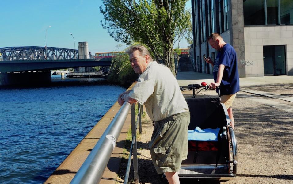 wei Männer stehen am Wasser, zwischen ihnen steht eine parkende Fahrradrikscha