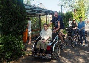 Zwei Männer sitzen auf einer Fahrradrikscha, einer fährt, der andere sitzt