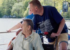 Zwei Männer sitzen auf einer Fahrradrikscha und schauen aufs Wasser