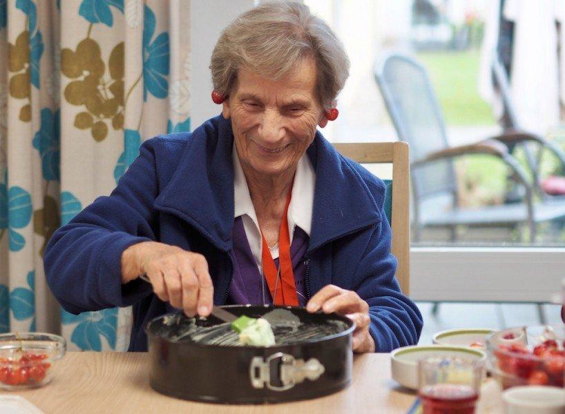 Eine ältere Dame füllt Kuchenteig in eine Form und hat sich Kirschen an die Ohren gehängt
