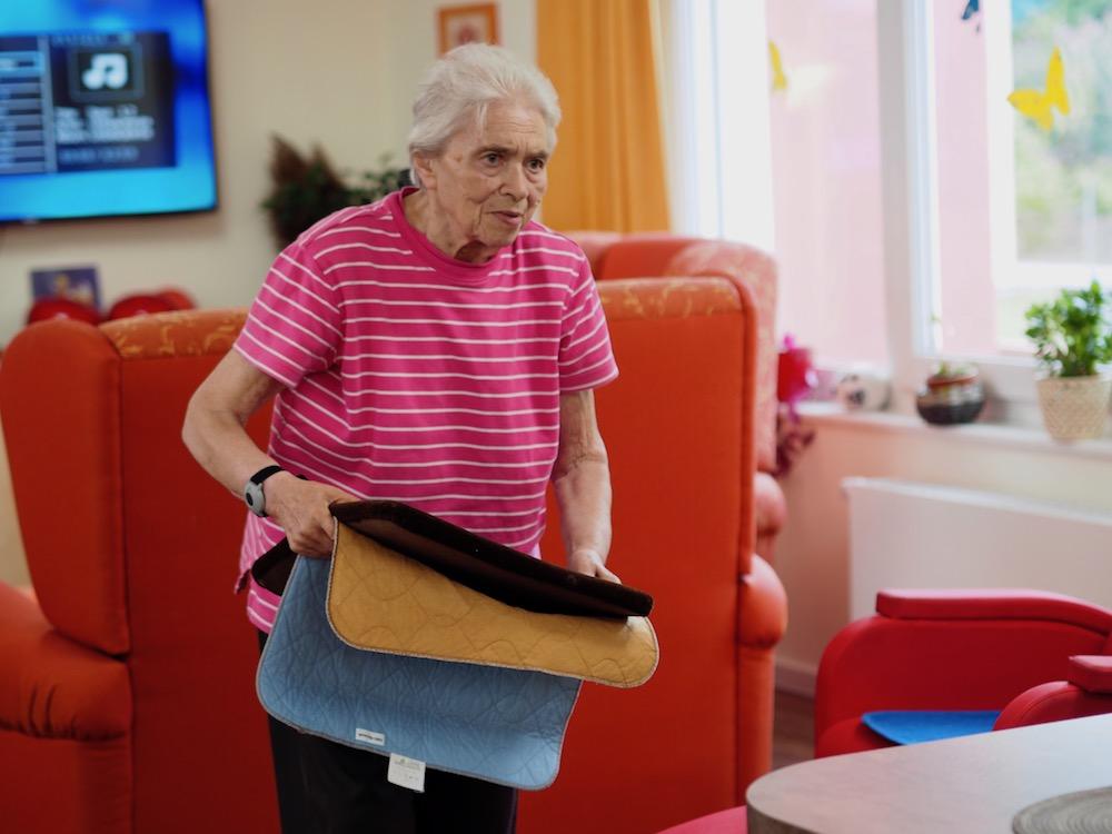 Eine alte Dame hält kleine Vorleger in der Hand