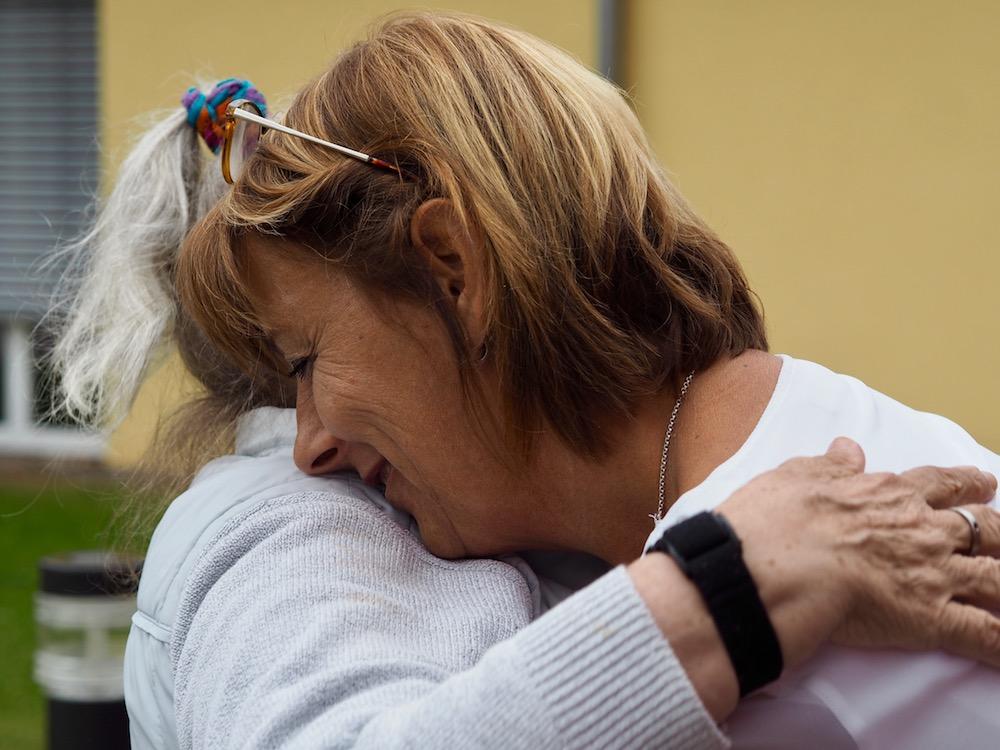 Eine alte Dame umarmt eine Frau