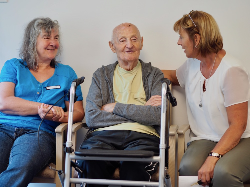 Ein alter Mann mit Rollator vor sich sitzt zwischen zwei Frauen