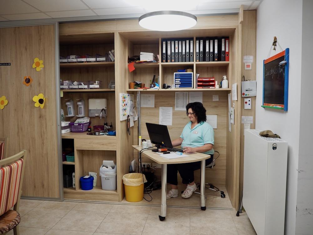 Eine Frau sitzt an einem Schreibtisch in einer Schrankwand mit Aktenordnern