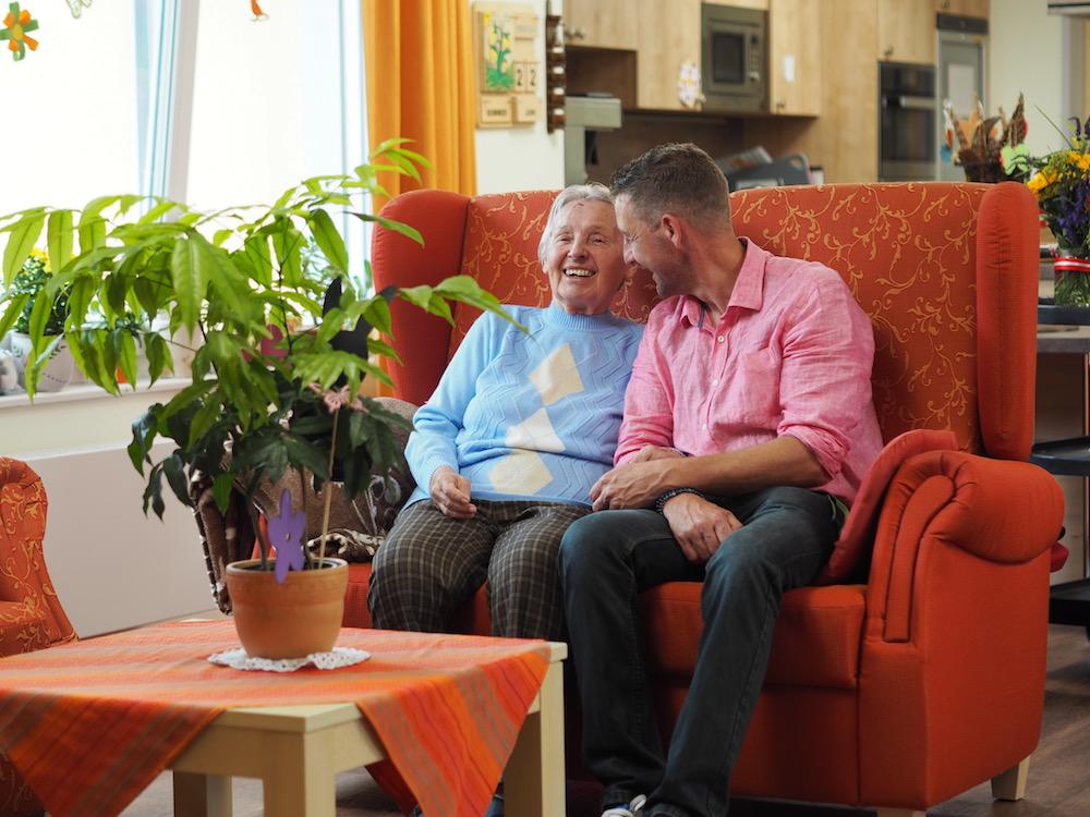 Eine alte Dame und ein Mann sitzen auf einem Sofa und unterhalten sich