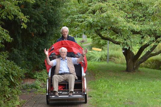 Der Ahrensburger Bürgermeister Michael Sarach fährt einen Bewohner durch den Park des Pflegeheims Tobias-Haus